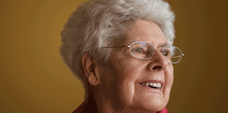 Portrait einer alten Dame mit weissen Harren und Brille, die lächelt.