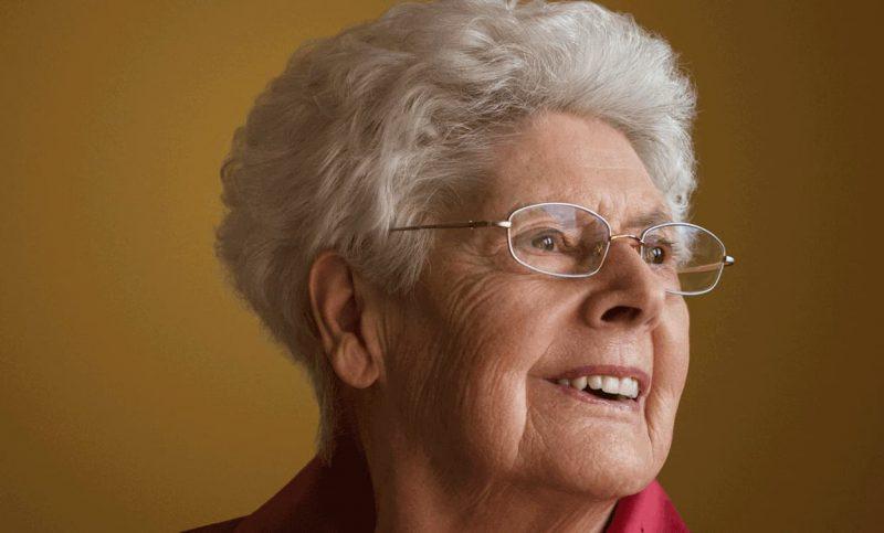Portrait d'une vieille dame aux cheveux blancs et aux lunettes qui sourit.