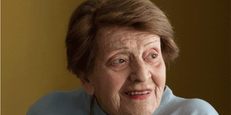 Portrait d'une vieille dame aux cheveux bruns qui sourit.