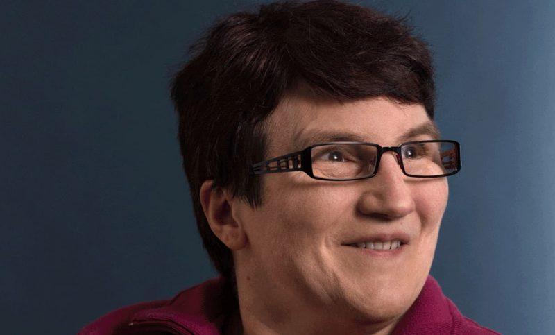 Portrait d'une dame aux cheveux bruns et aux lunettes souriantes.