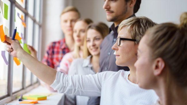 Team Erarbeitet Ideen Und Klebt Zettel An Ein Fenster